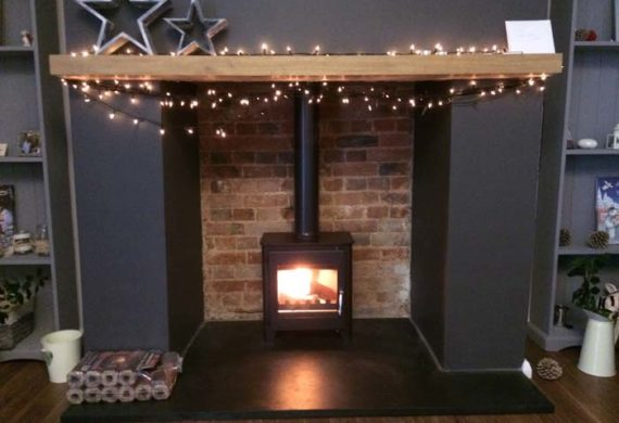 wood burning stove installed into a home with fairy lights around the fire place