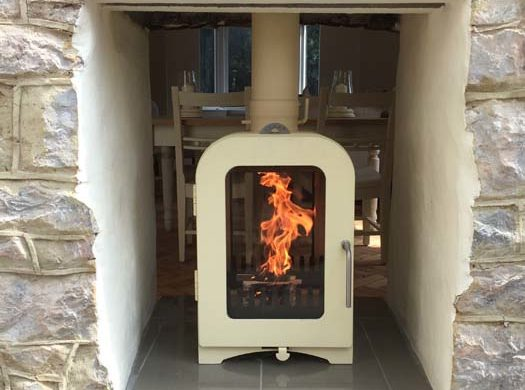 modern wood burner installed into stone fireplace