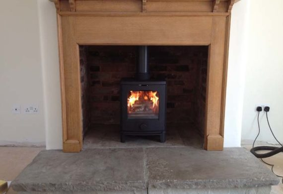 new log burner in wooden surround fireplace