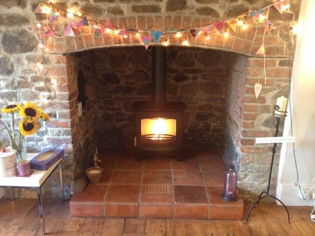 new log burner in brick surround fireplace