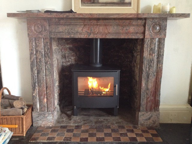 wood burner installed into a brick fire place