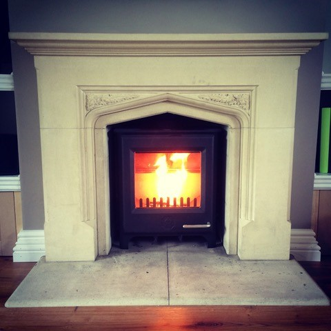 wood burning stove fitted into a marble fireplace